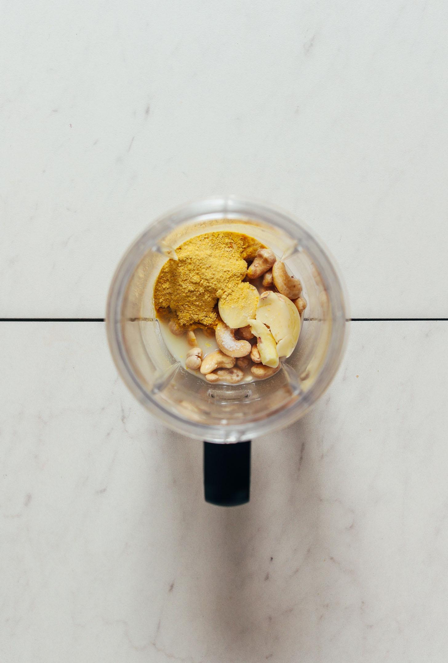 Liquidificador pequeno com ingredientes para fazer molho de massa de caju vegan