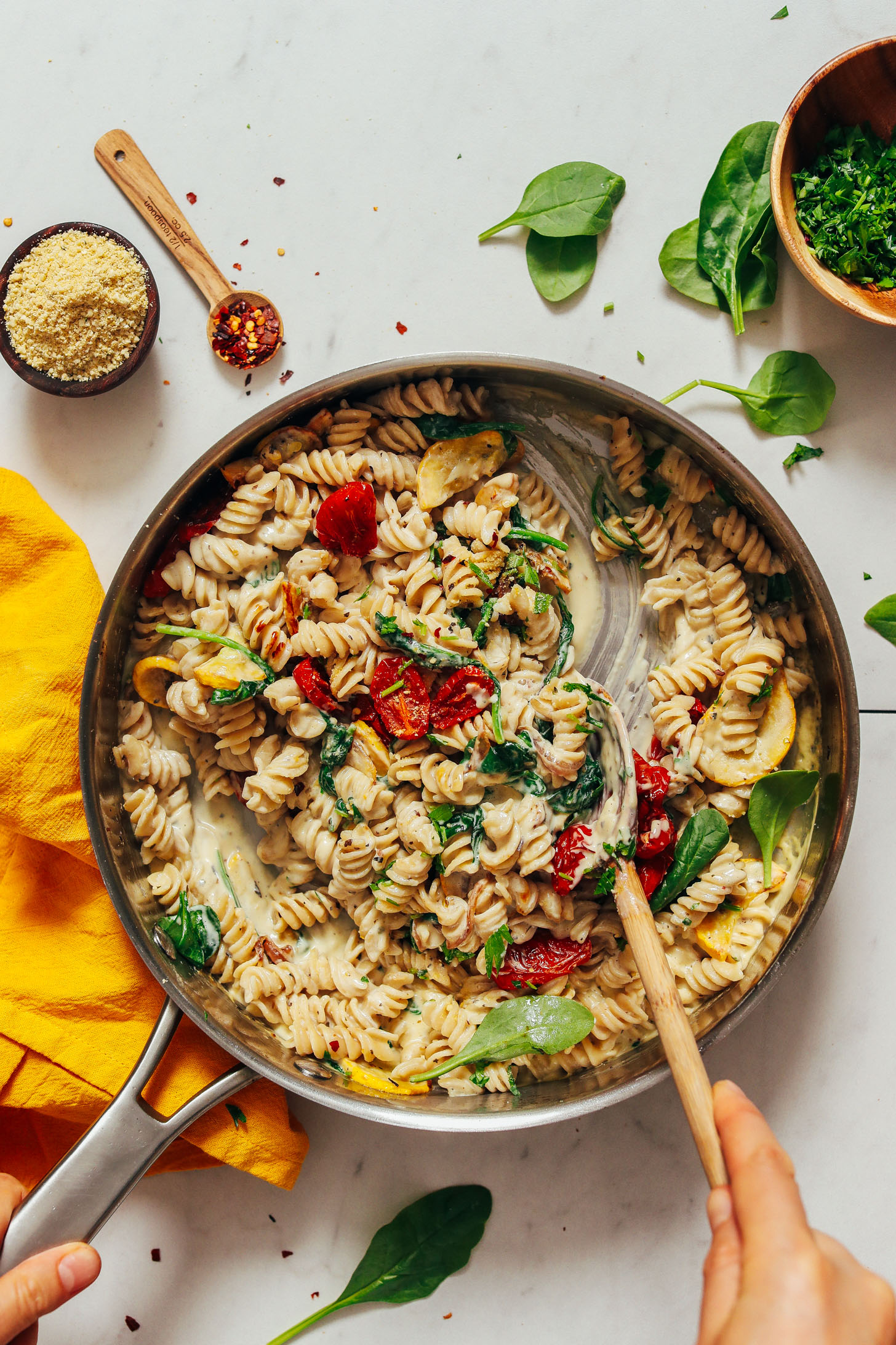 Using a wooden spoon to stir a pan of Creamy Vegan White Pasta with Summer Vegetables