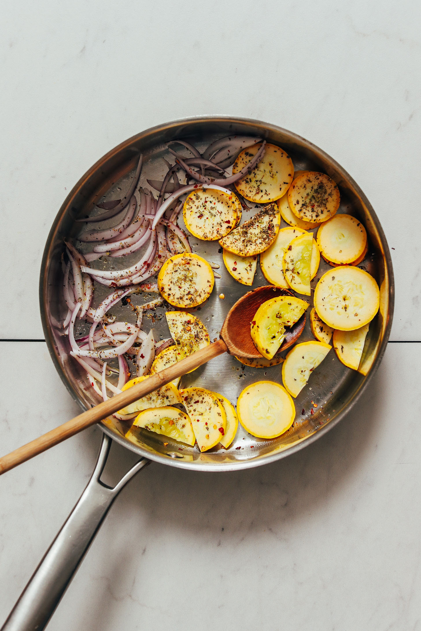Sautéing yellow squash and red onion in a skillet with Italian seasonings