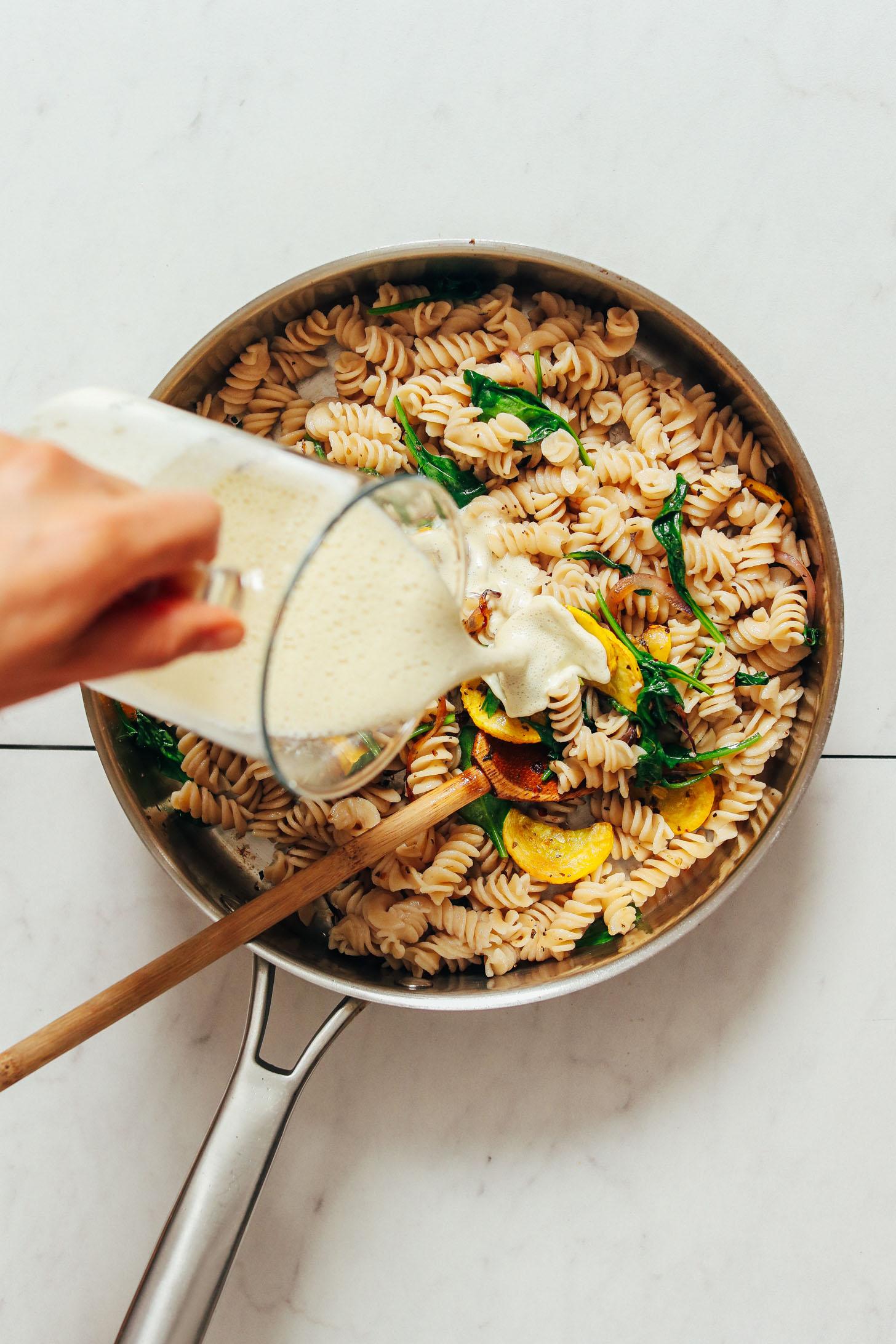 Pouring creamy cashew alfredo onto pasta and sautéed veggies