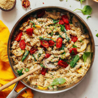 Wooden spoon resting in a pot of Creamy Vegan White Pasta with Summer Vegetables