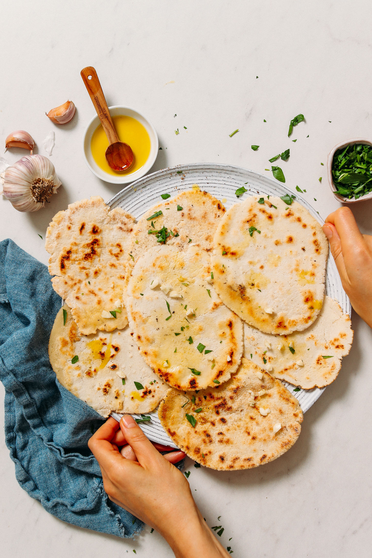 Holding a platter of gluten free naan topped with olive oil, garlic, and fresh parsley