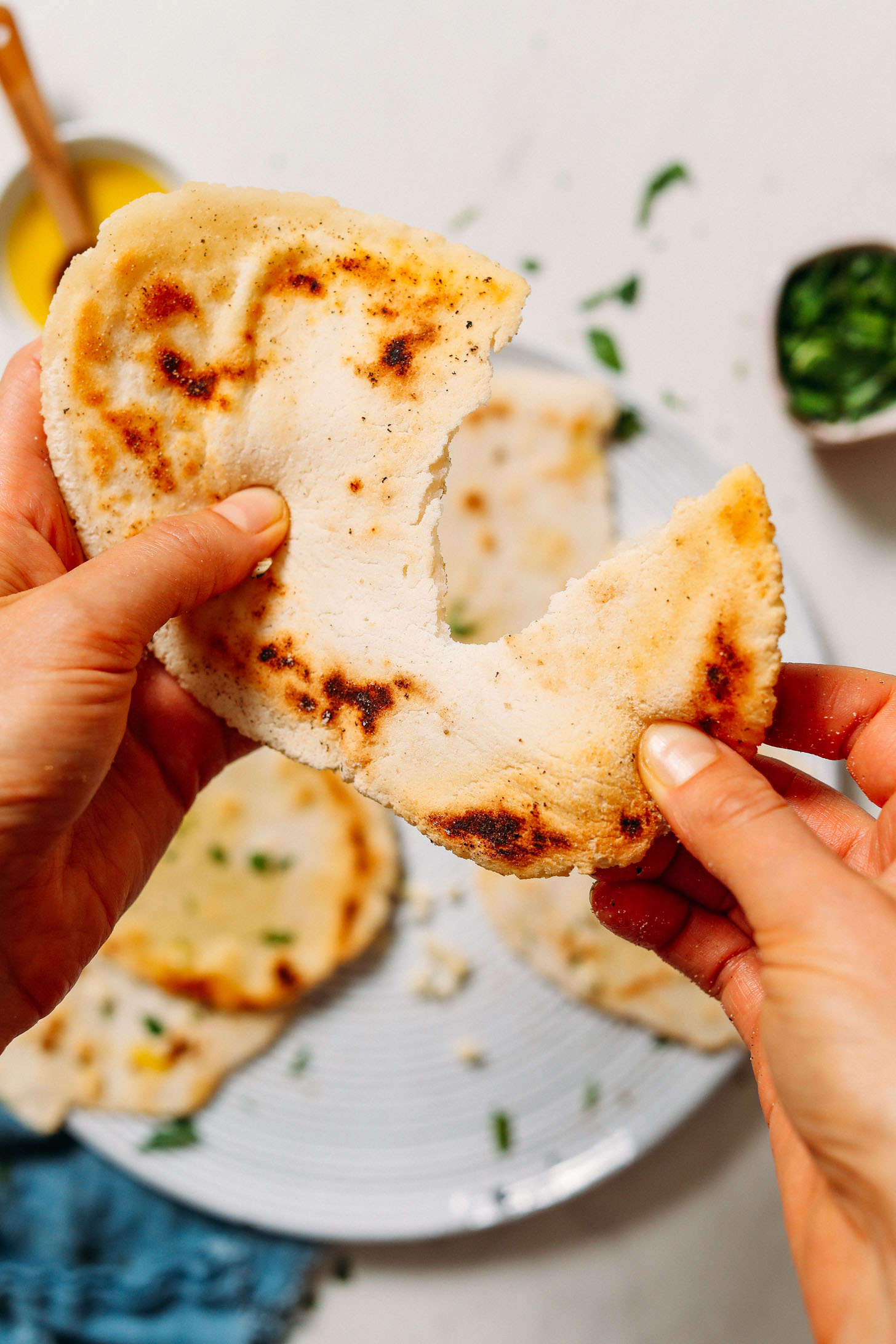 Pulling apart a piece of stretchy gluten free naan bread