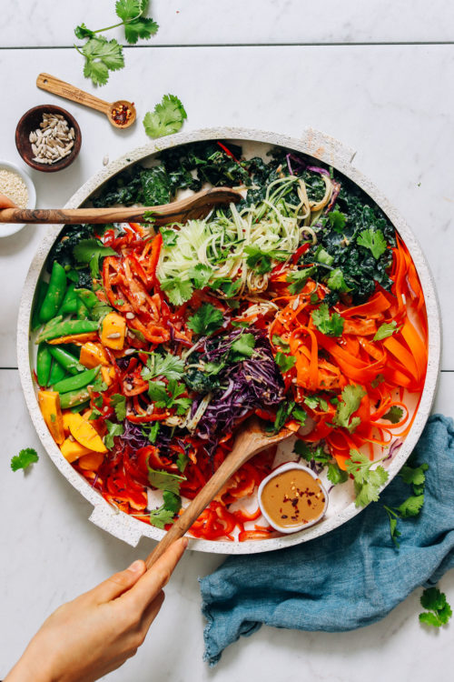 Using wooden tongs to pick up a serving of Veggie Noodle Salad with Peanut Dressing