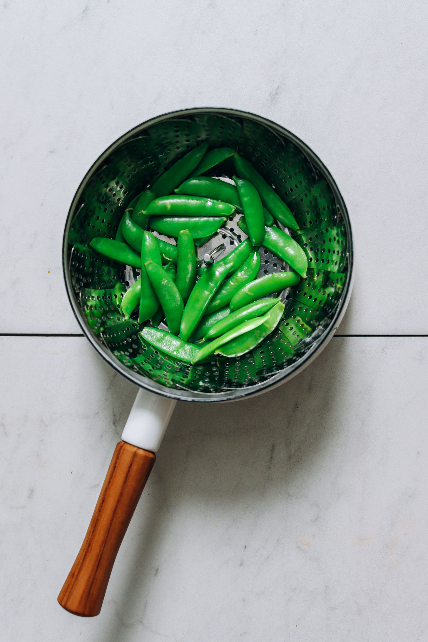 Steaming snow peas in a small saucepan