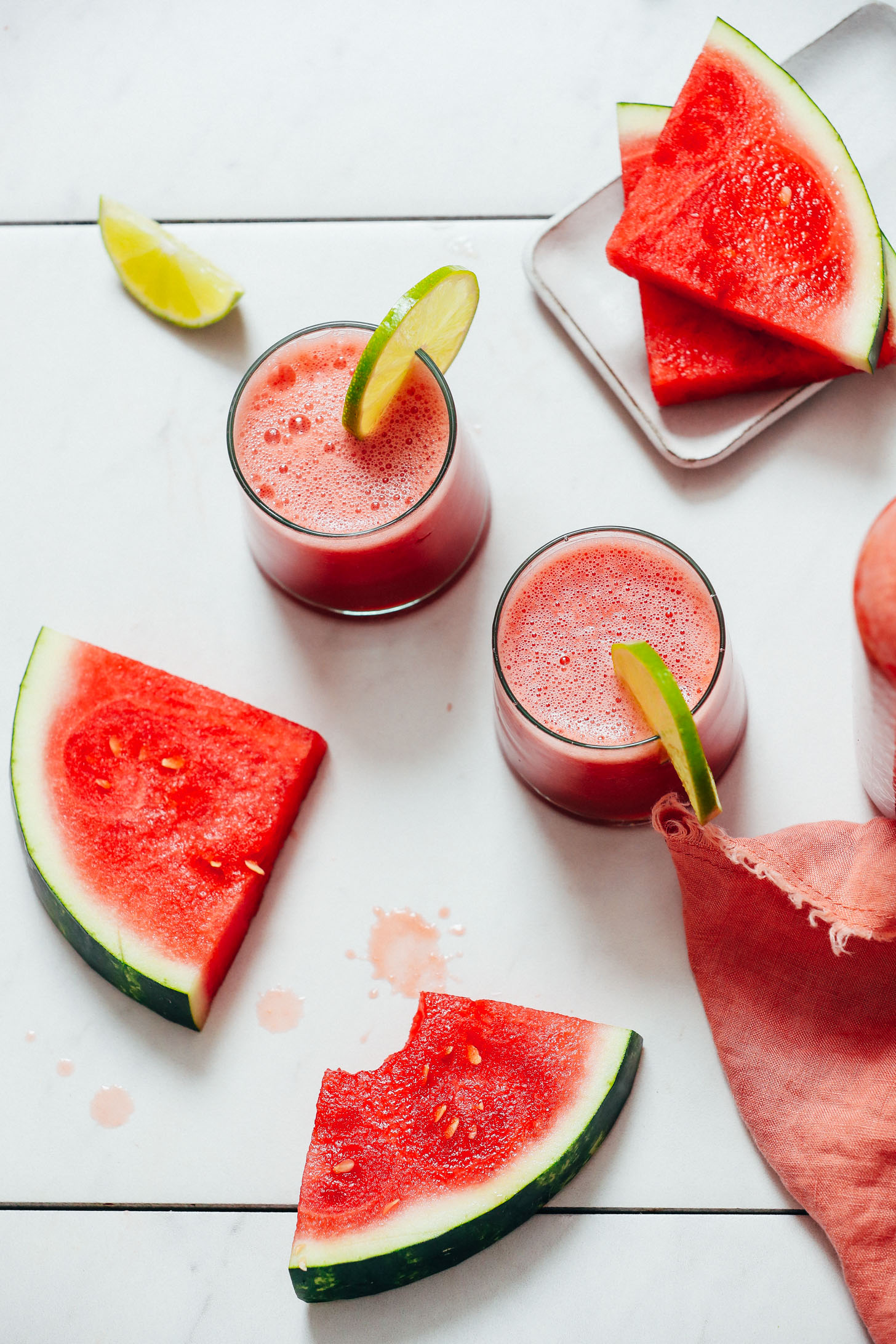 Watermelon slices next to two glasses of watermelon juice