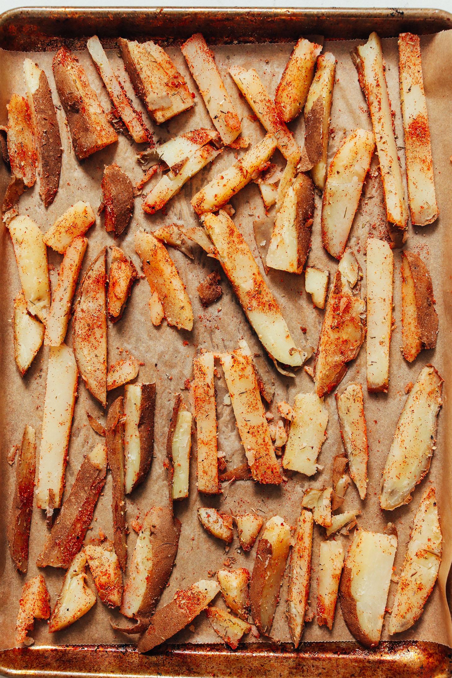 Papas fritas cajún sin hornear en una bandeja para hornear forrada de pergamino