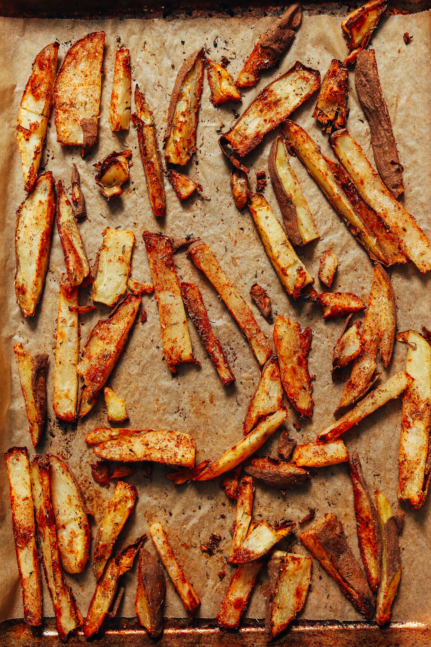 Parchment-lined baking sheet of oil-free fries with cajun seasonings