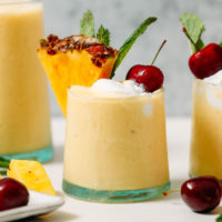 Vegan piña coladas topped with coconut whipped cream, pineapple, mint, and cherries