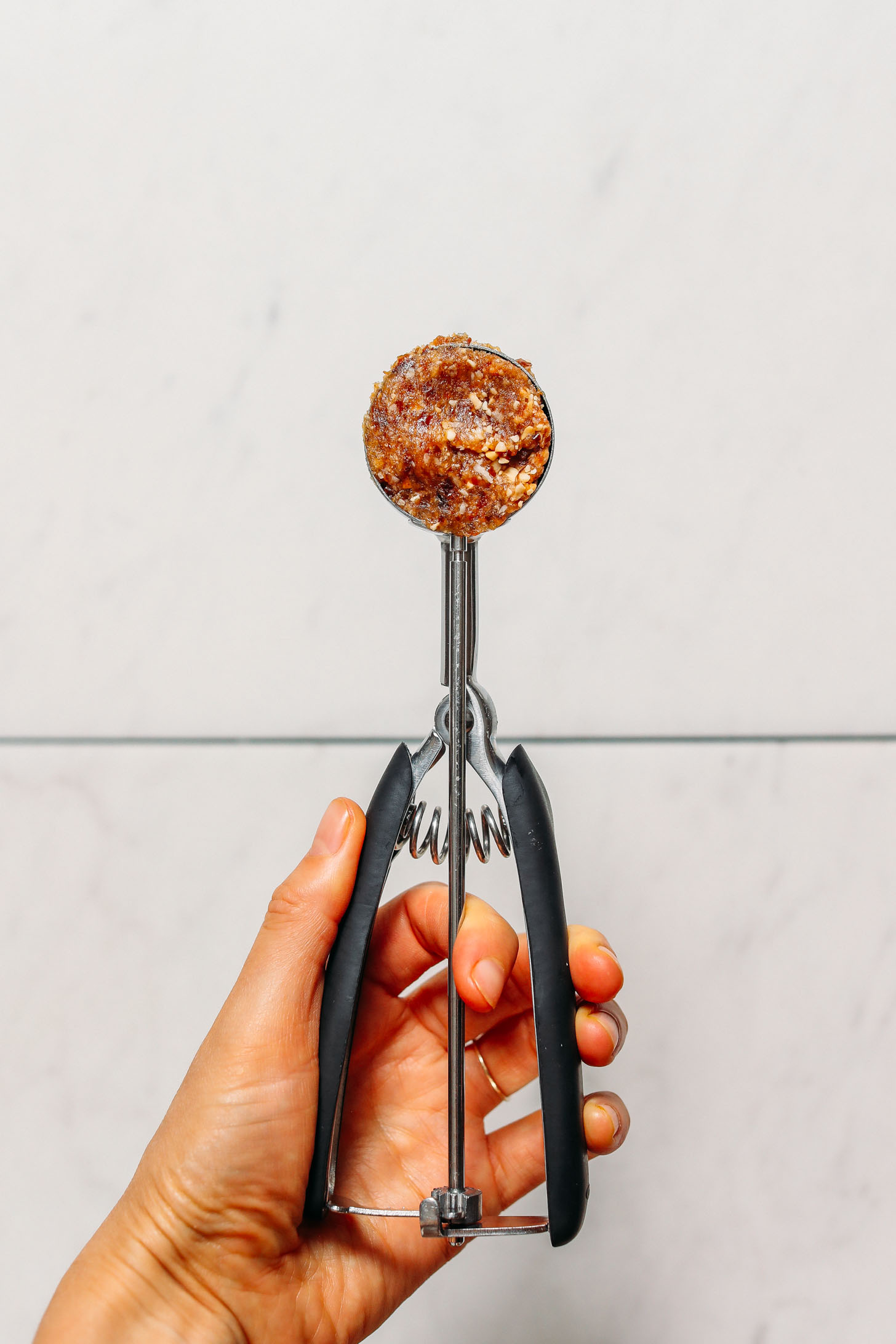Salted Cashew Caramel Energy Bite dough in a small cookie scoop