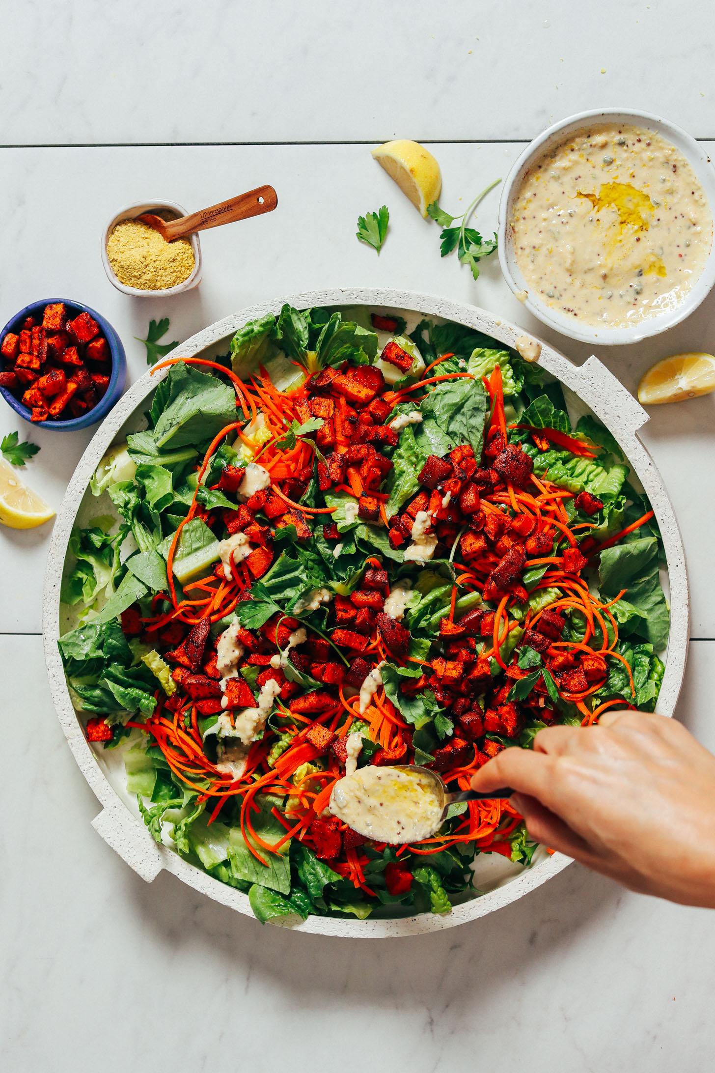 Usando uma colher para regar o Molho Vegan Caesar em um prato de salada
