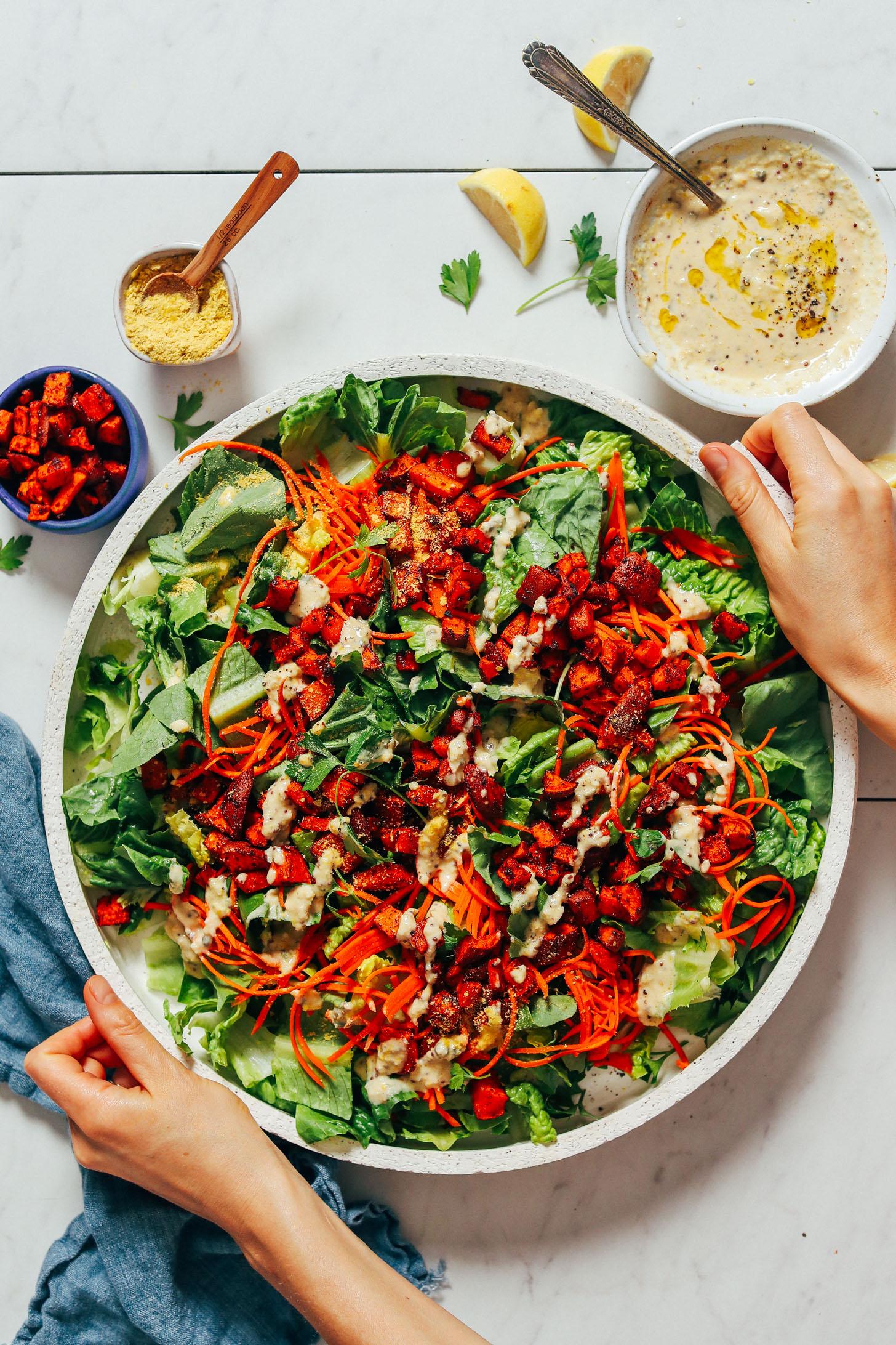 Prato grande de Salada César Vegan ao lado de fermento nutricional, molho de homus e croutons de batata doce