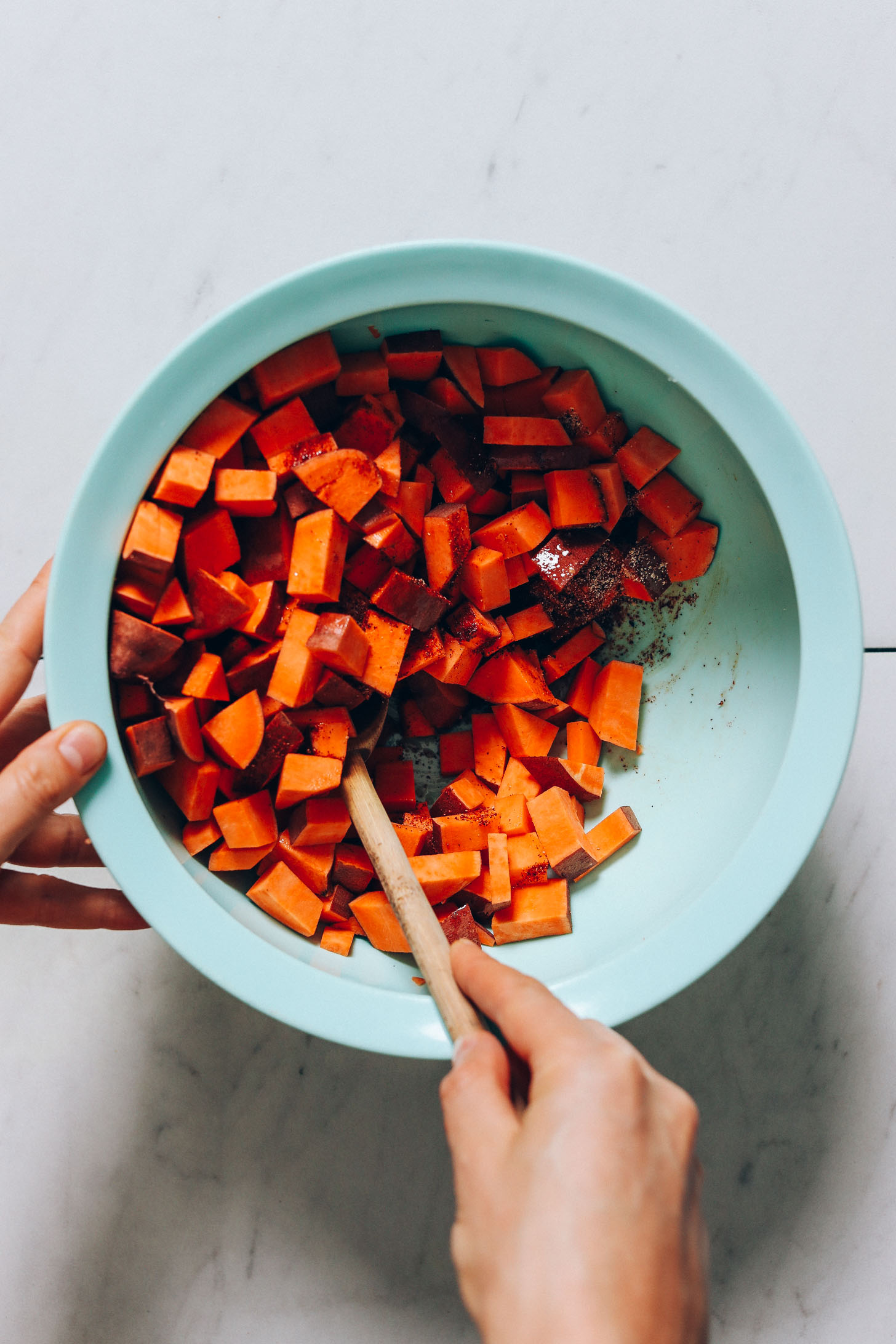 Stirring cubed sweet potatoes with oil and BBQ spices
