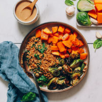 Bowl of roasted butternut squash, miso brussels sprouts, and millet next to tahini sauce, garlic, and vegetables