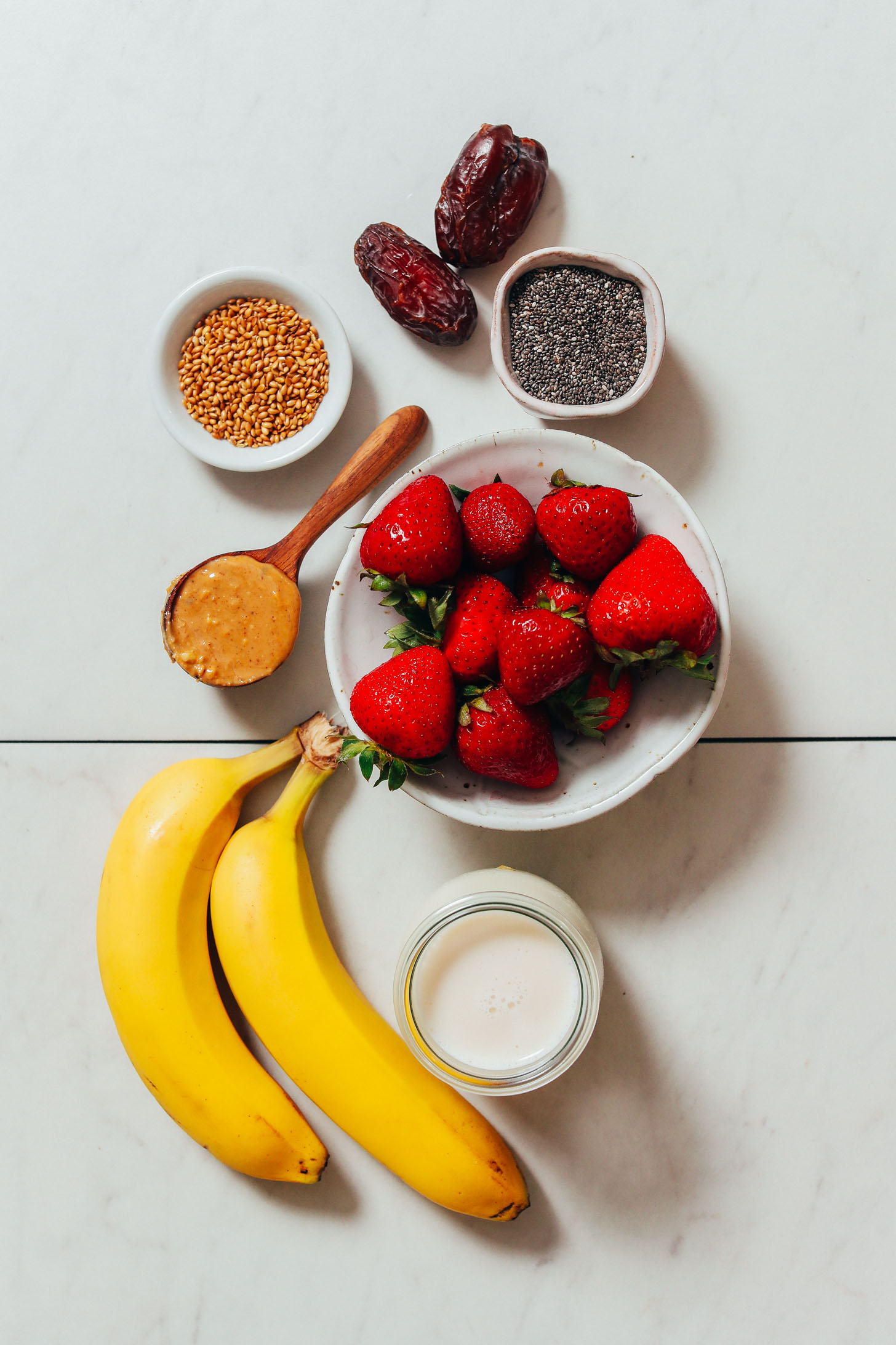 Dates, chia seeds, flax seeds, peanut butter, bananas, strawberries, and dairy-free milk