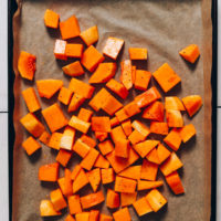 Parchment-lined baking sheet with cubed butternut squash