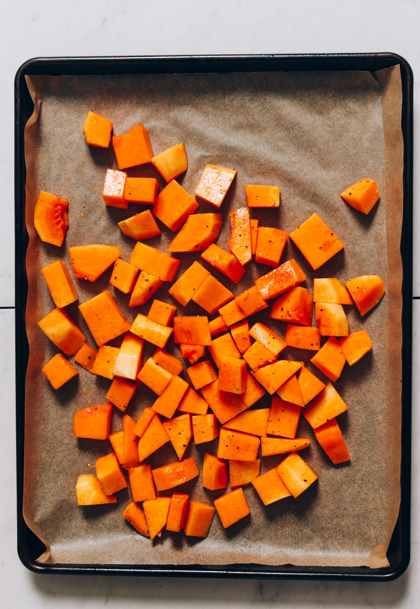 Cubed butternut squash seasoned with avocado oil, maple syrup, salt, and pepper