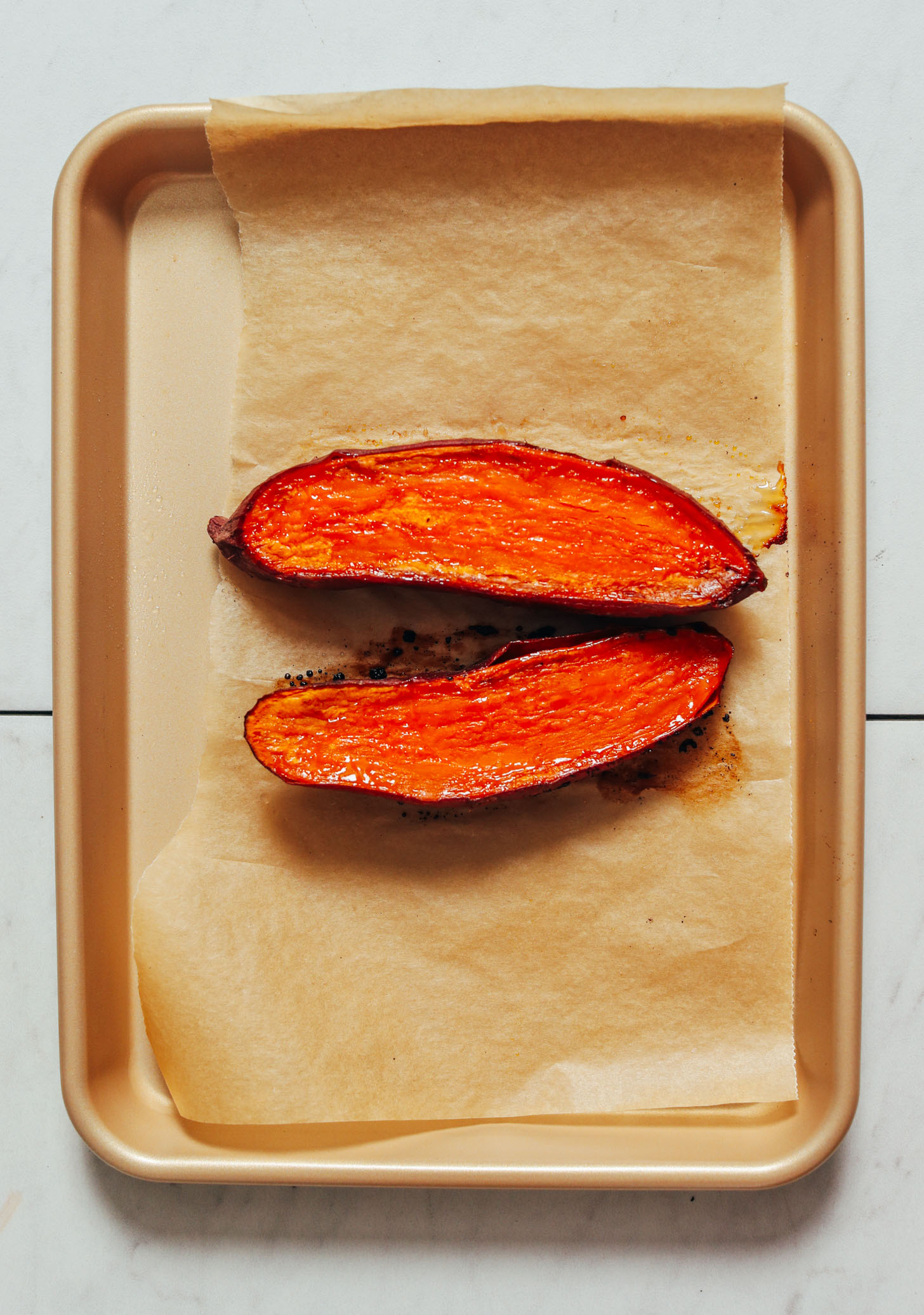 Baking sheet with a halved roasted sweet potato
