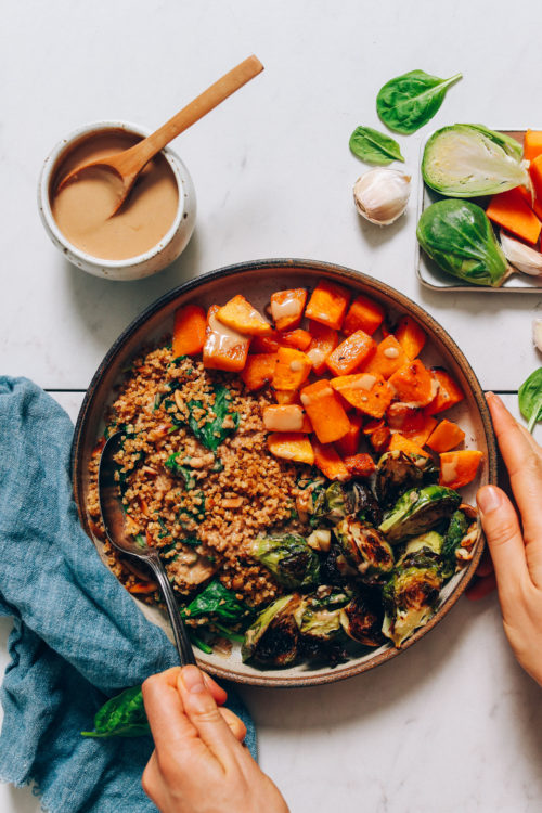 Butternut Squash & Miso Brussels Sprouts Bowl next to a bowl of tahini sauce