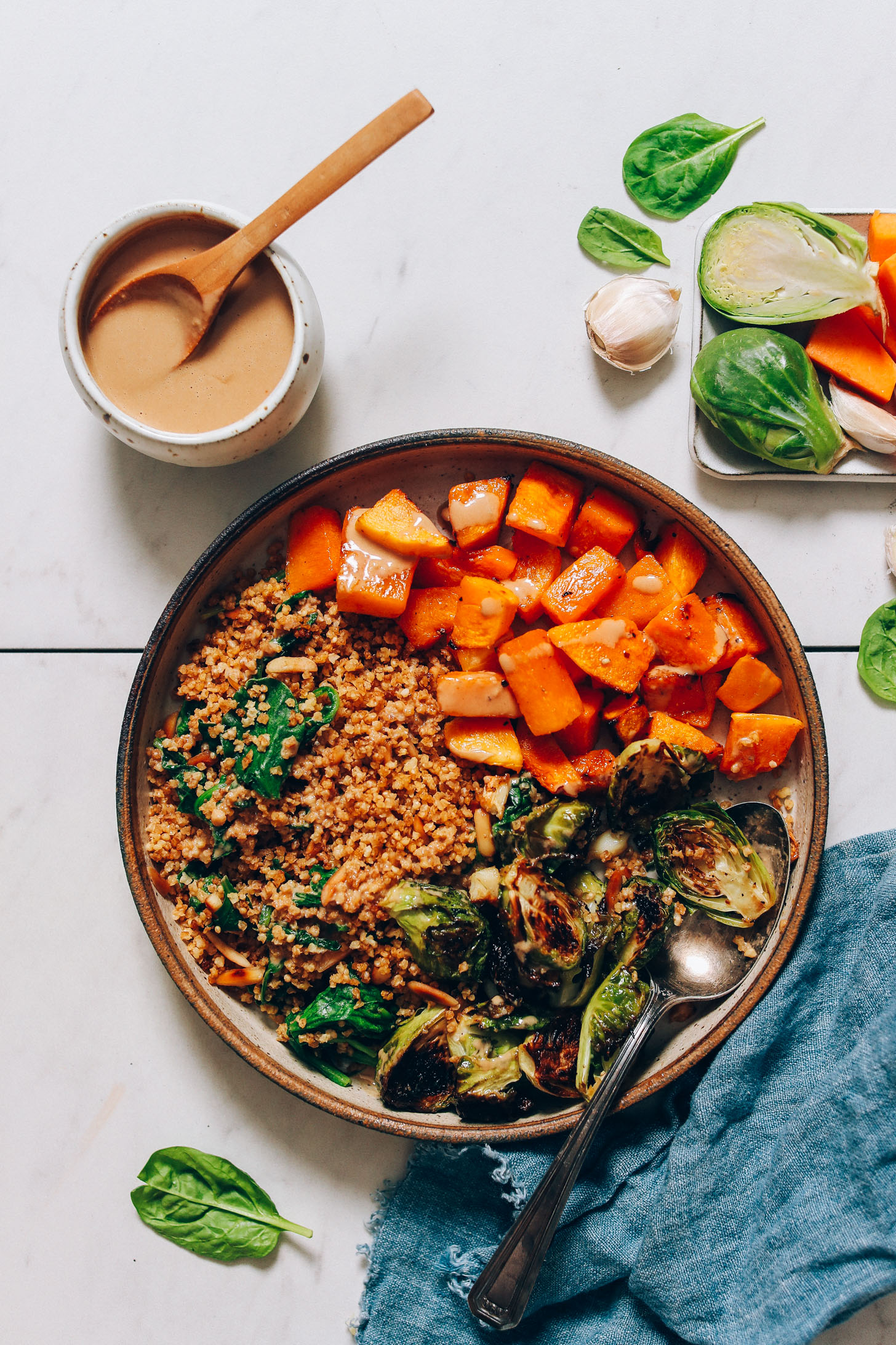 Fall nourish bowl made with squash, brussels sprouts, millet, and garlicky tahini sauce