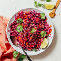 Bowl of Cabbage Slaw topped with fresh cilantro and lime