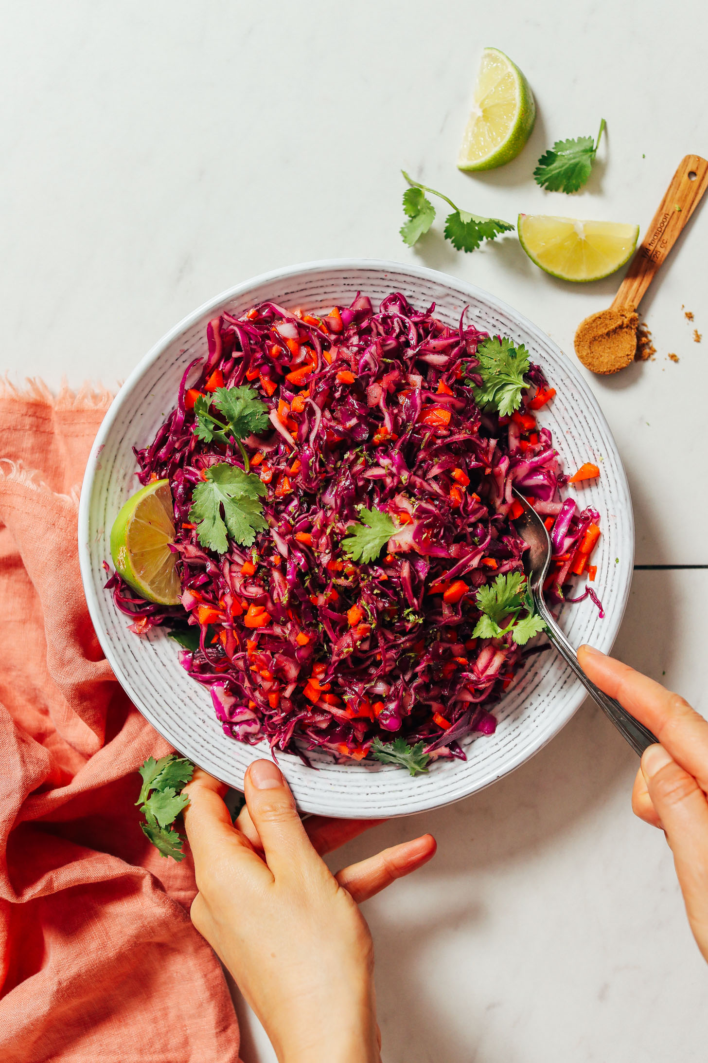 Using a spoon to stir a bowl of Quick Citrusy Cabbage Slaw