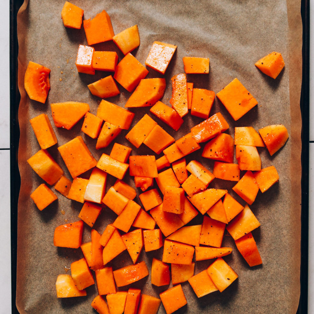 Cubed butternut squash on a parchment-lined baking sheet