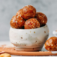 Bowl filled with Salted Cashew Caramel Energy Bites topped with shredded coconut