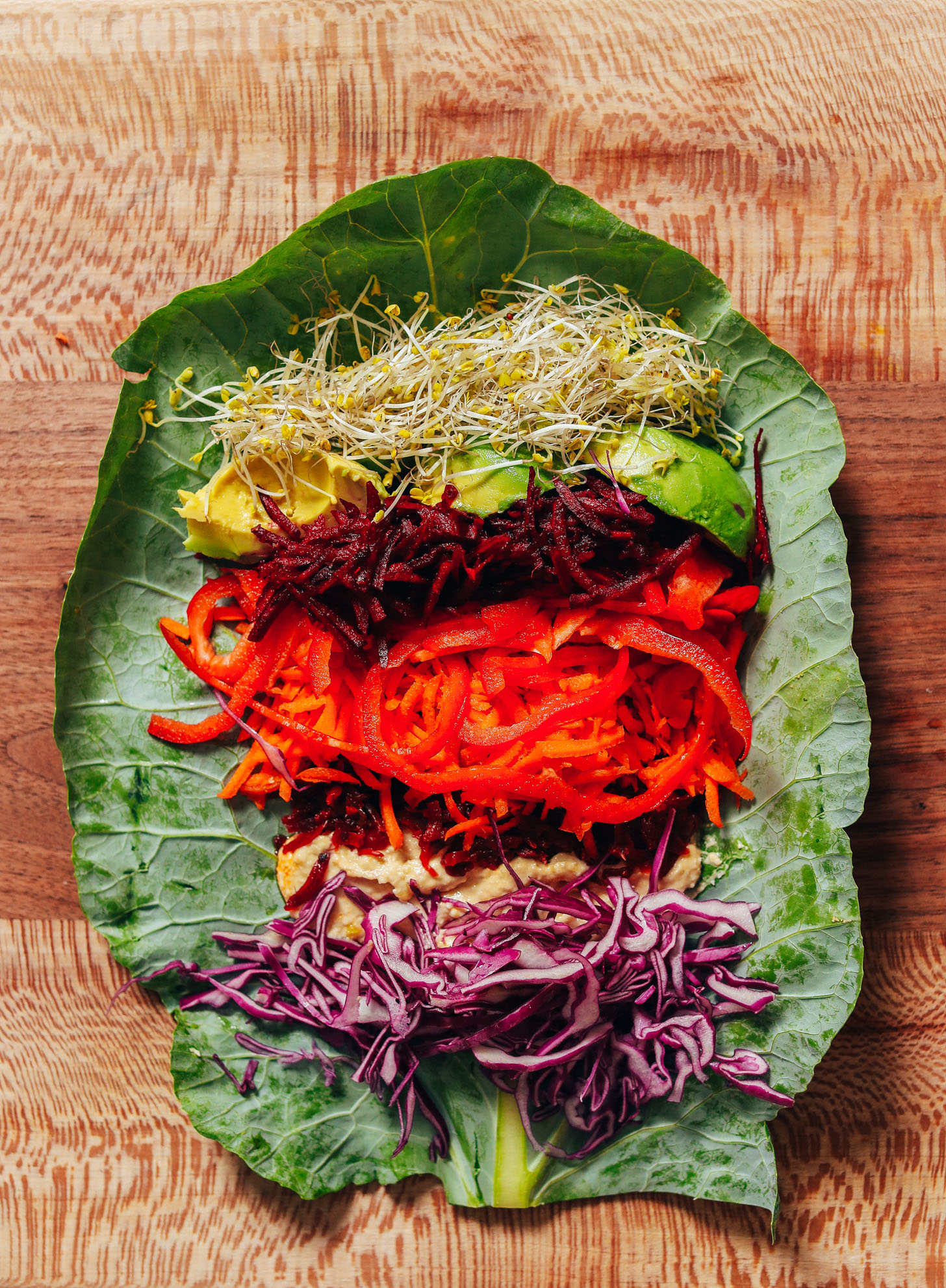 Cutting board with a collard grean leaf topped with broccoli sprouts, avocado, shredded beet, carrot, bell pepper, sauerkraut, hummus, and cabbage