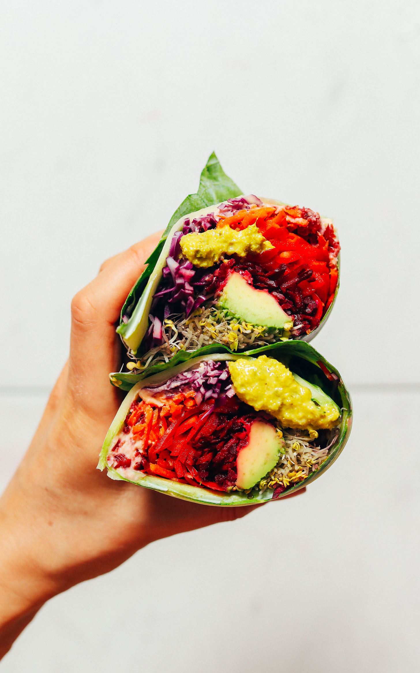 Holding up a Collard Wrap filled with fresh veggies and green curry tahini sauce