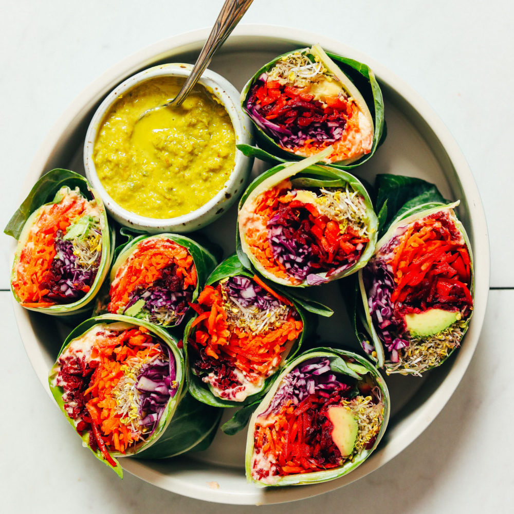 Veggie collard wraps with a bowl of Green Curry Tahini Sauce