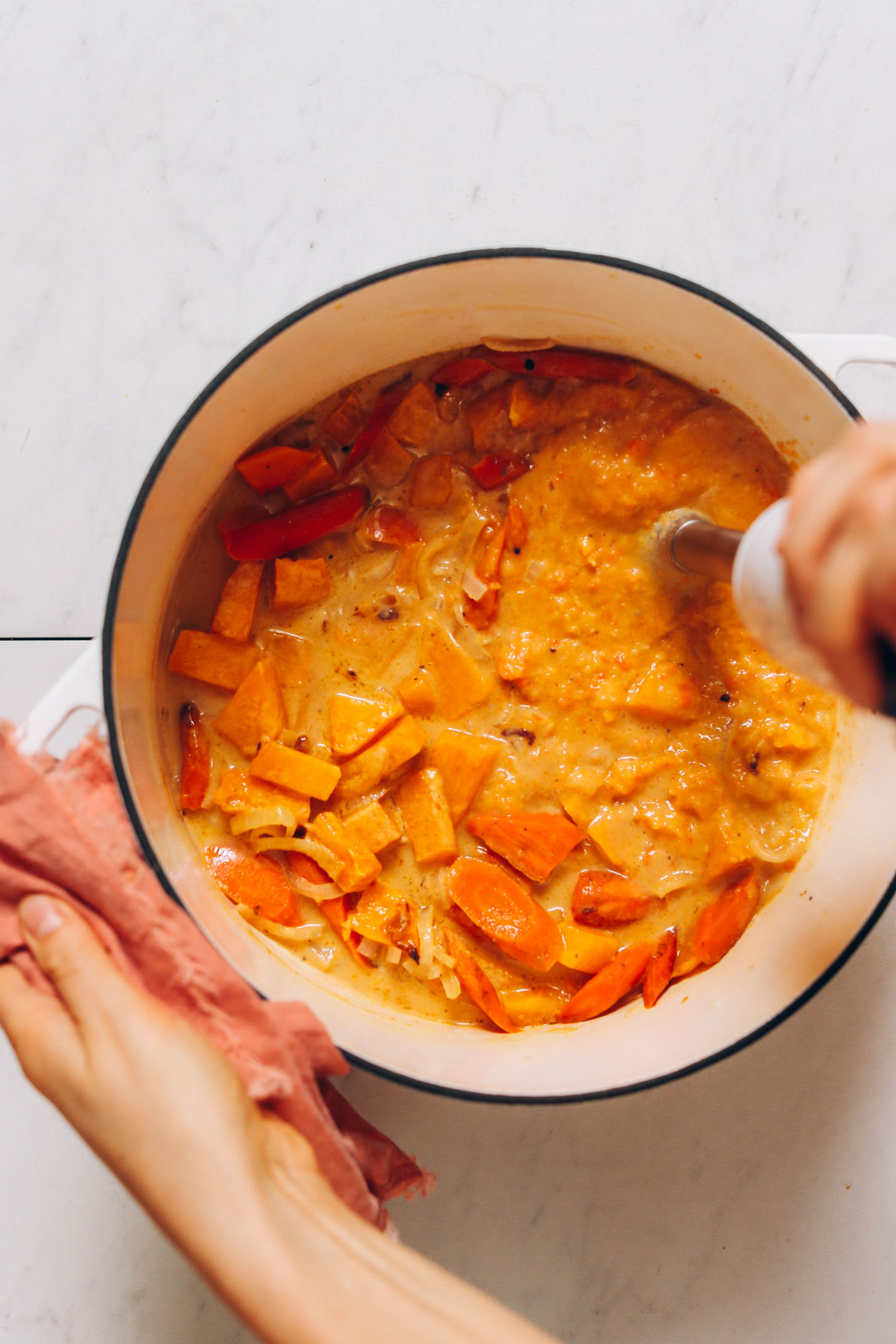 Using an immersion blender to purée a pot of roasted butternut squash soup