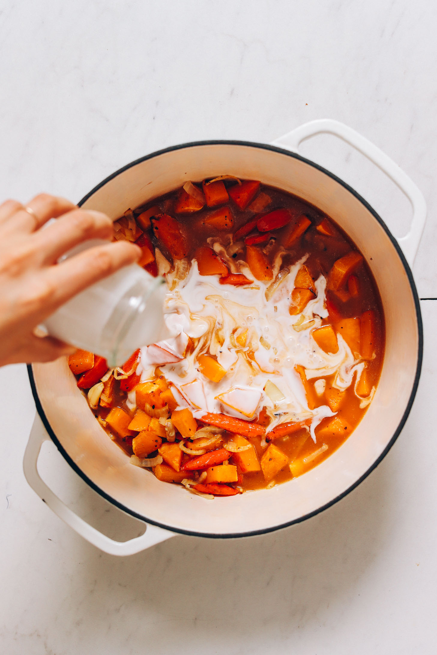 Pouring coconut milk into a pot with carrots, butternut squash, garlic, onion, and vegetable broth