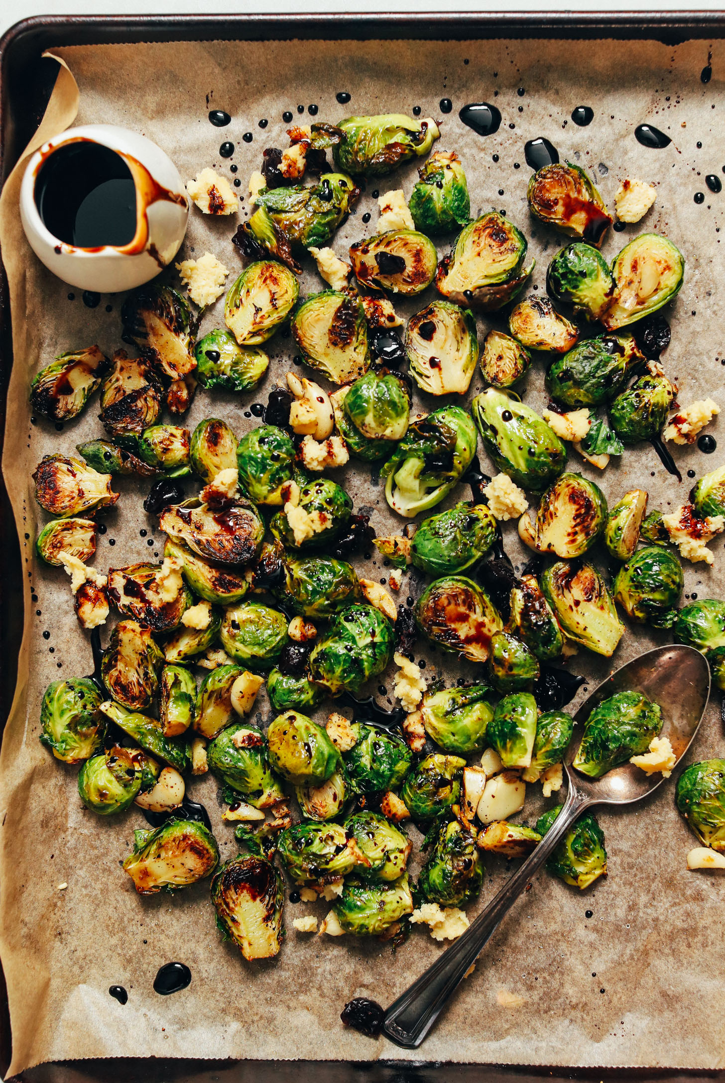 Baking sheet of roasted Brussels sprouts drizzled with balsamic reduction