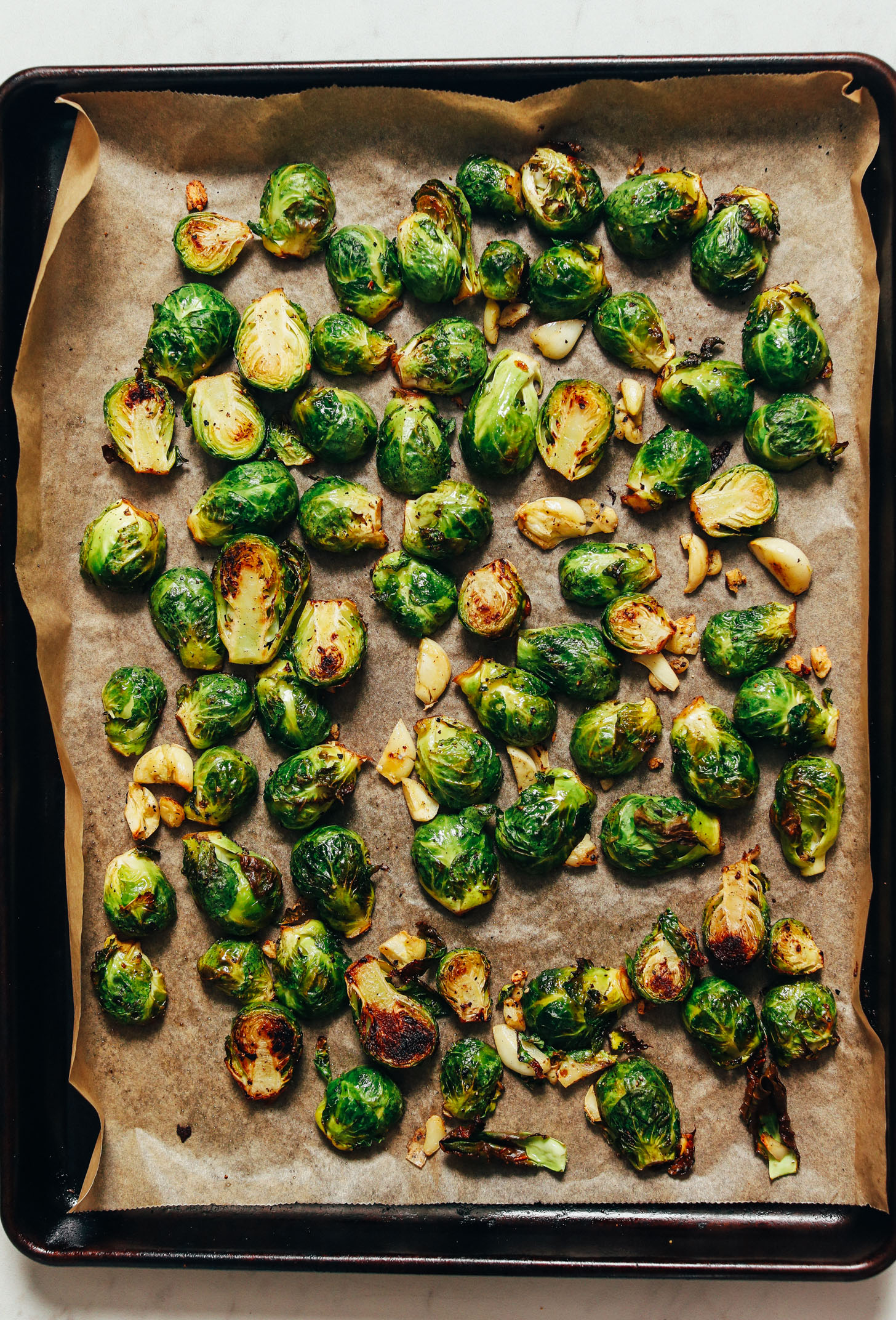 Parchment-lined baking sheet of roasted Brussels sprouts