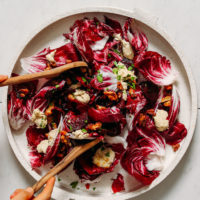 Using salad tongs to pick up a serving of radicchio salad