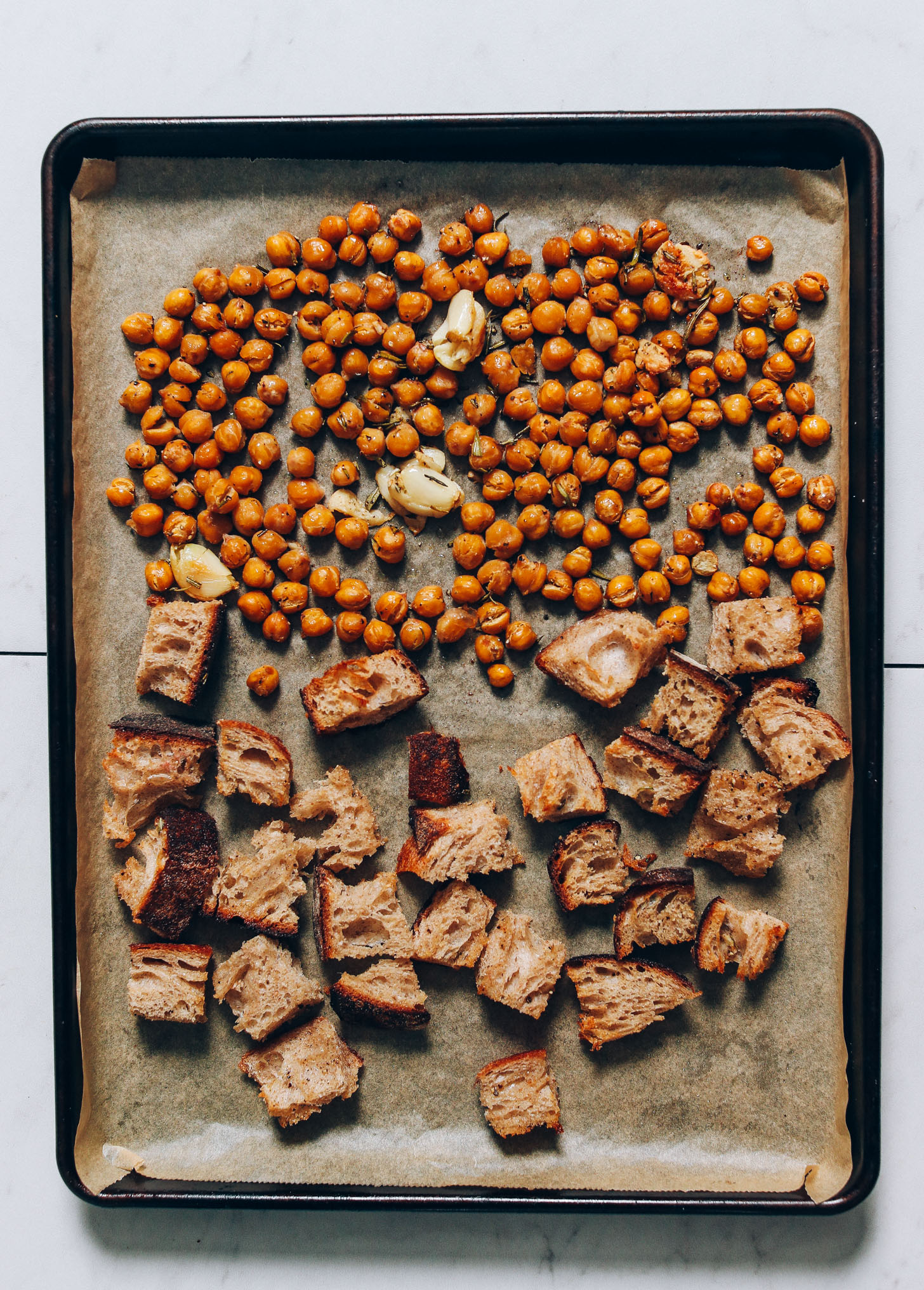 Parchment-lined baking sheet of crusty bread, garlic cloves, and chickpeas