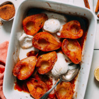 Baking dish of Easy Baked Pears with scoops of vegan vanilla ice cream