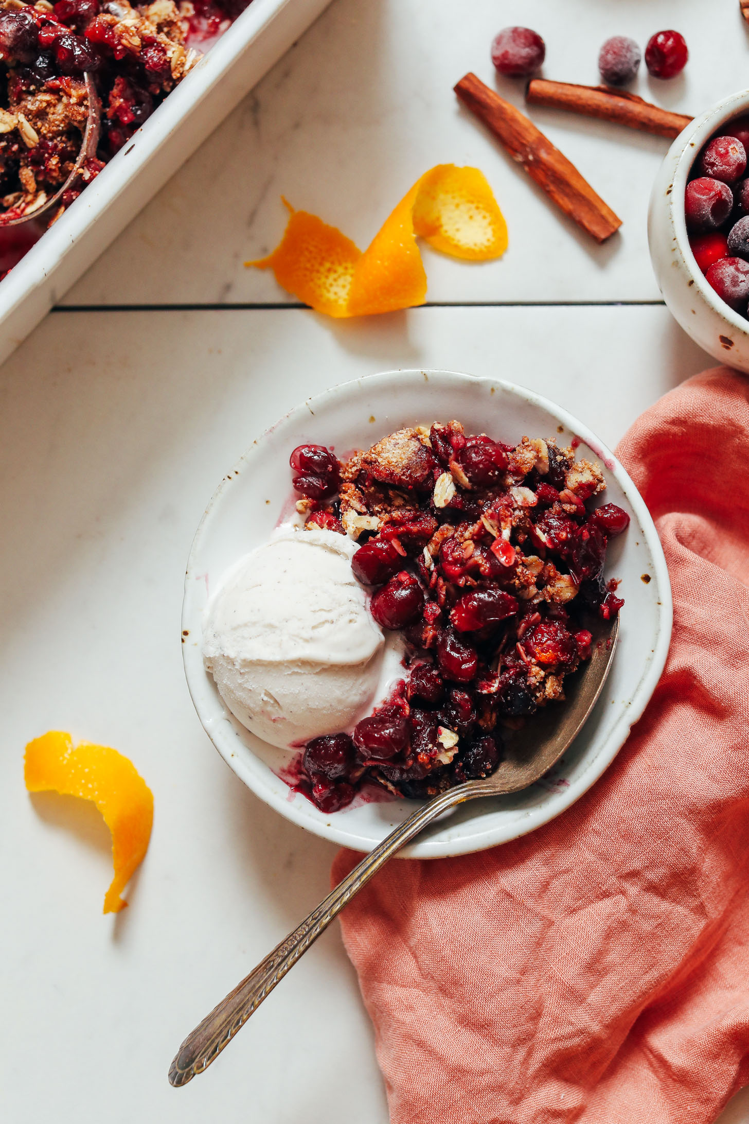 Spoon in a bowl of gluten-free cranberry crisp with vegan vanilla ice cream