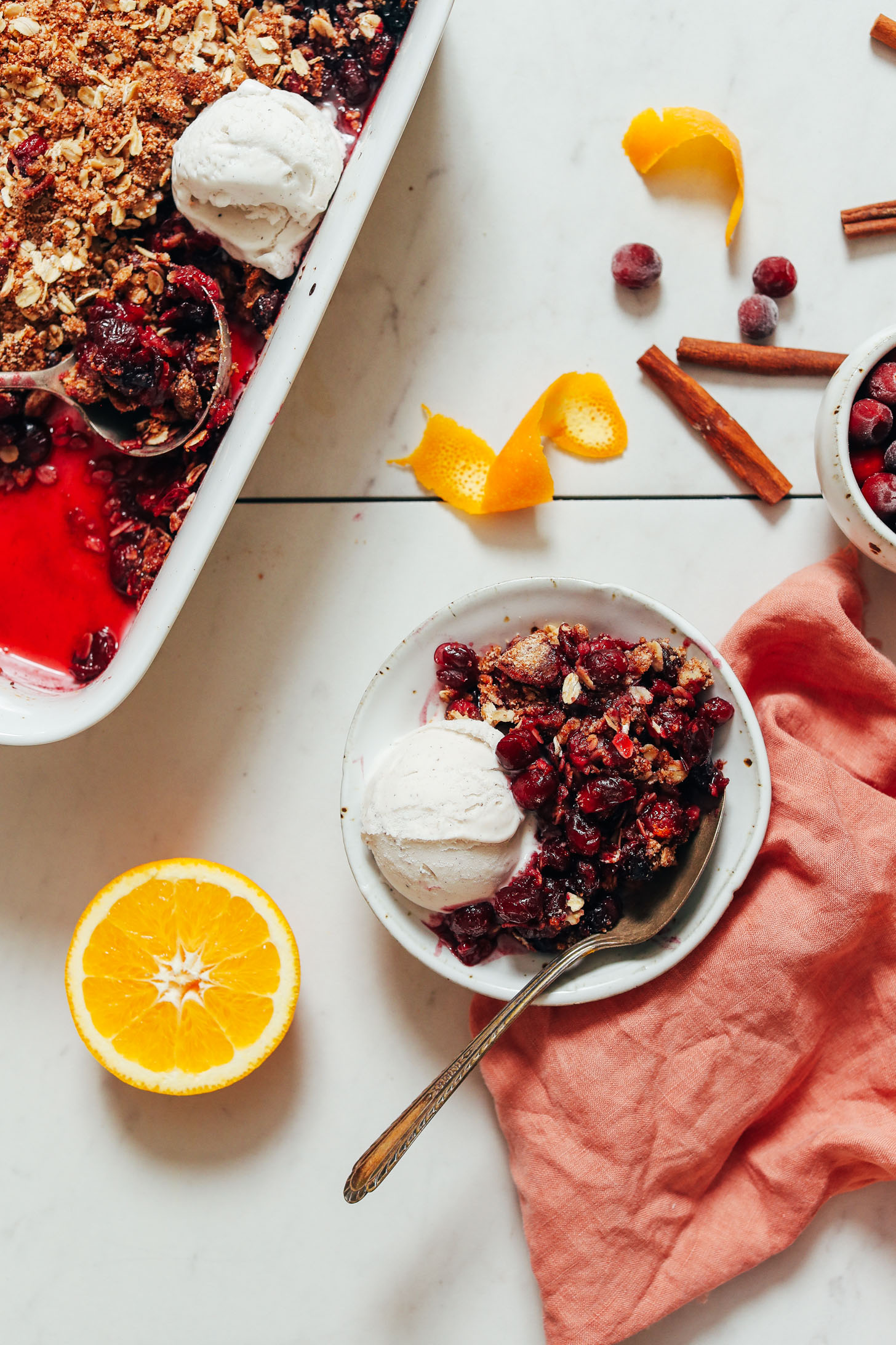 Bowl and baking dish of orange cranberry crisp with vegan vanilla ice cream