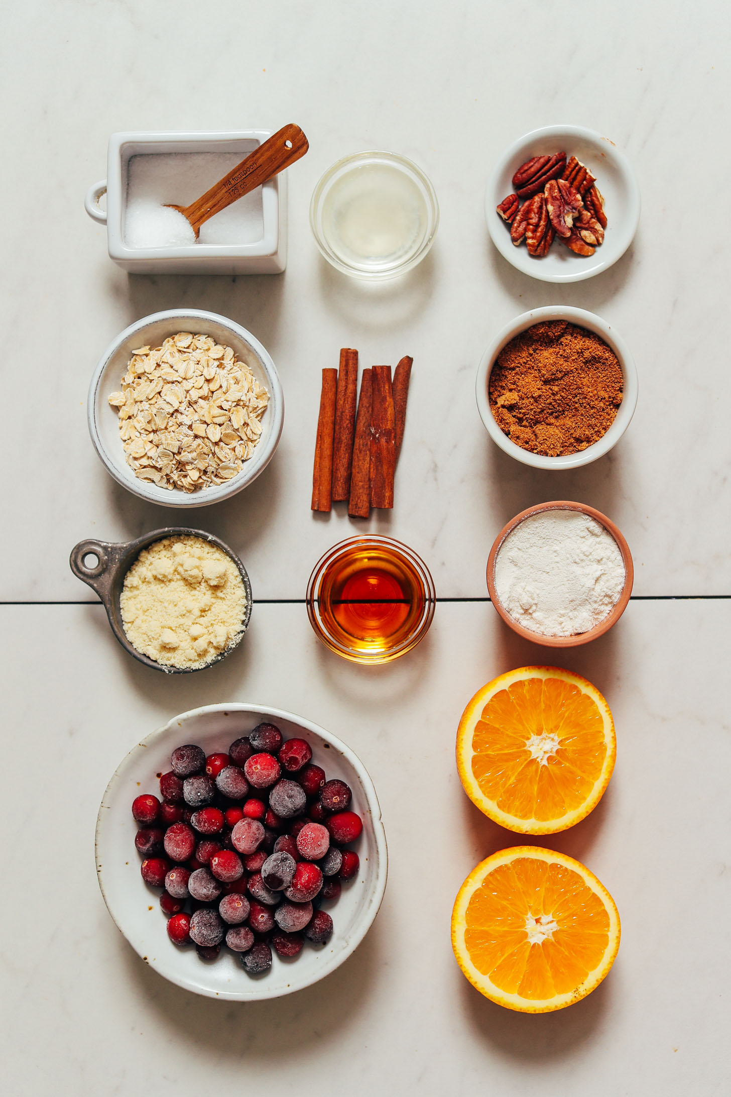 Laranjas, cranberries, farinha de amêndoa, xarope de bordo, mistura de farinha sem glúten, aveia, paus de canela, açúcar de coco, óleo de coco e sal marinho