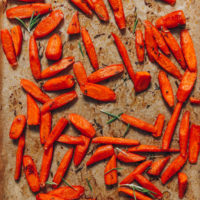 Parchment-lined baking sheet of perfect roasted carrots with fresh herbs