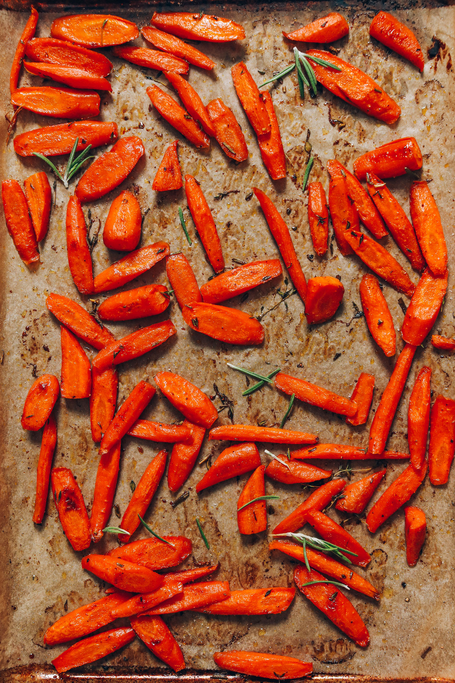 Baking sheet of roasted carrots with rosemary and thyme