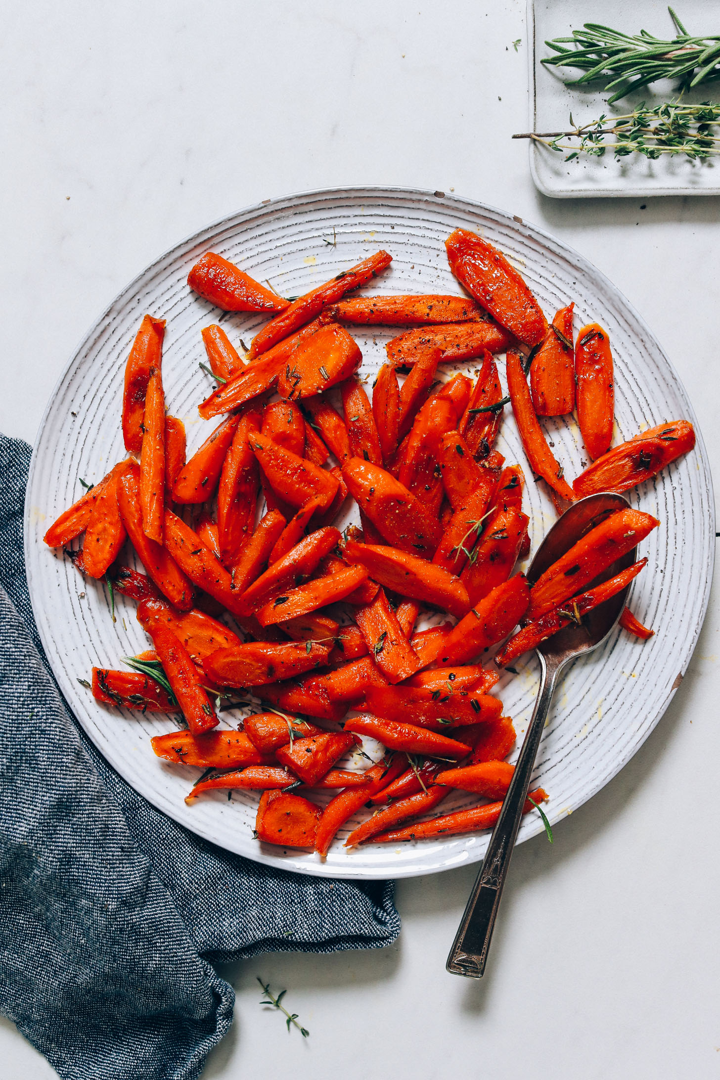 Platter of roasted carrots with fresh thyme and rosemary