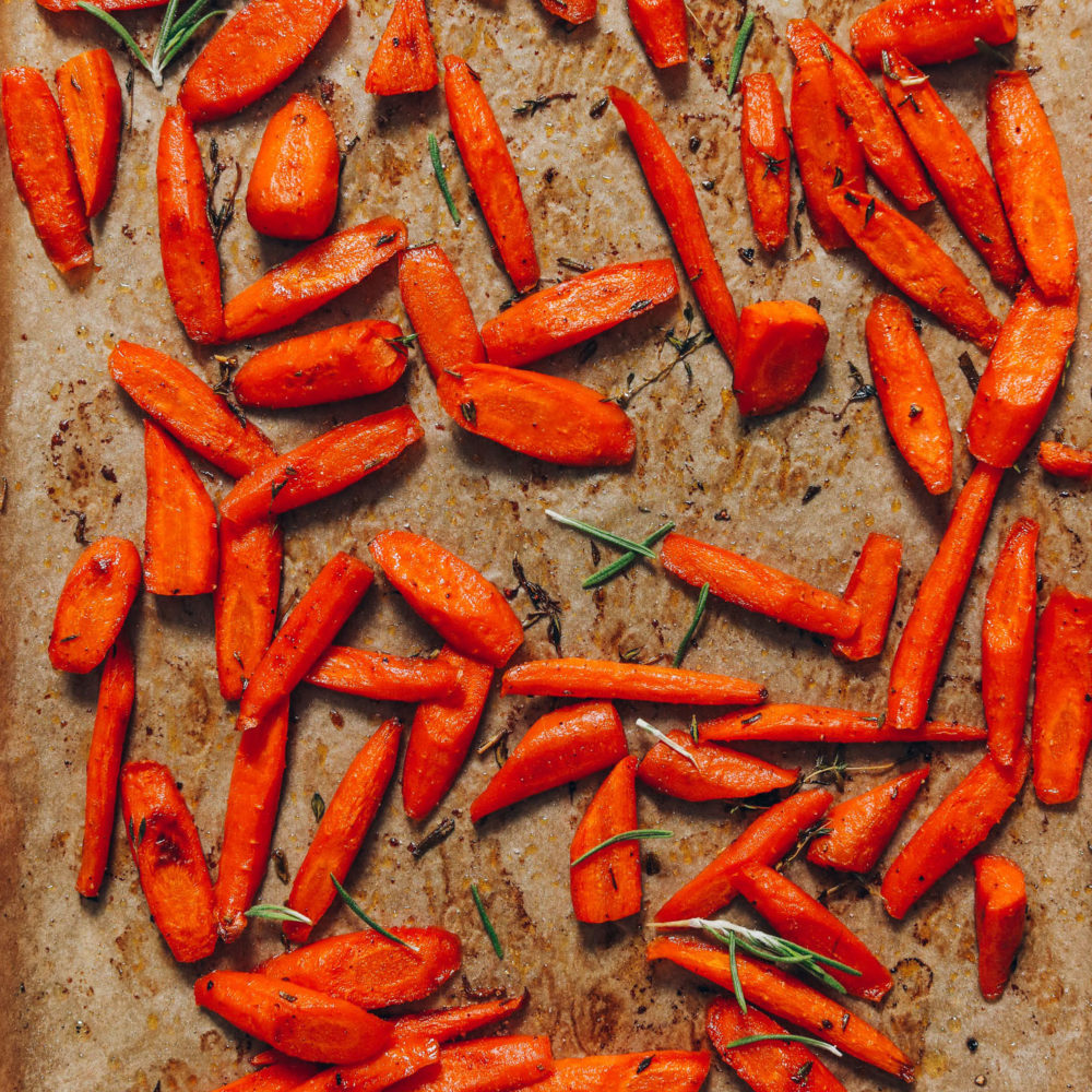 Baking sheet of perfect roasted carrots with fresh rosemary and thyme