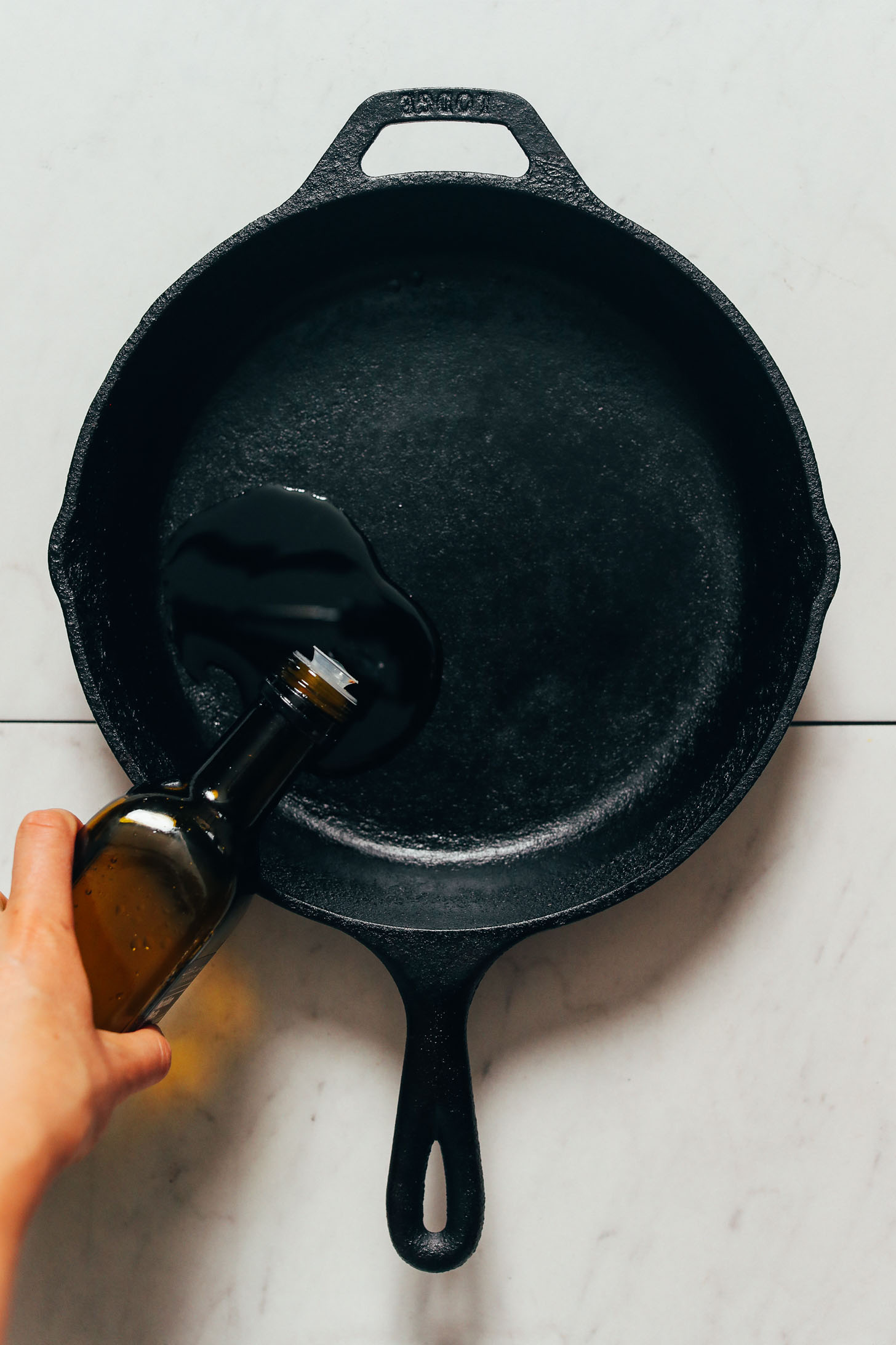 Pouring oil into a cast iron skillet
