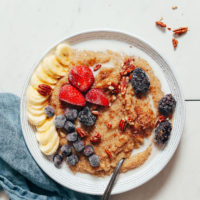 Bowl of amaranth with dairy-free milk, fresh fruit, and pecans