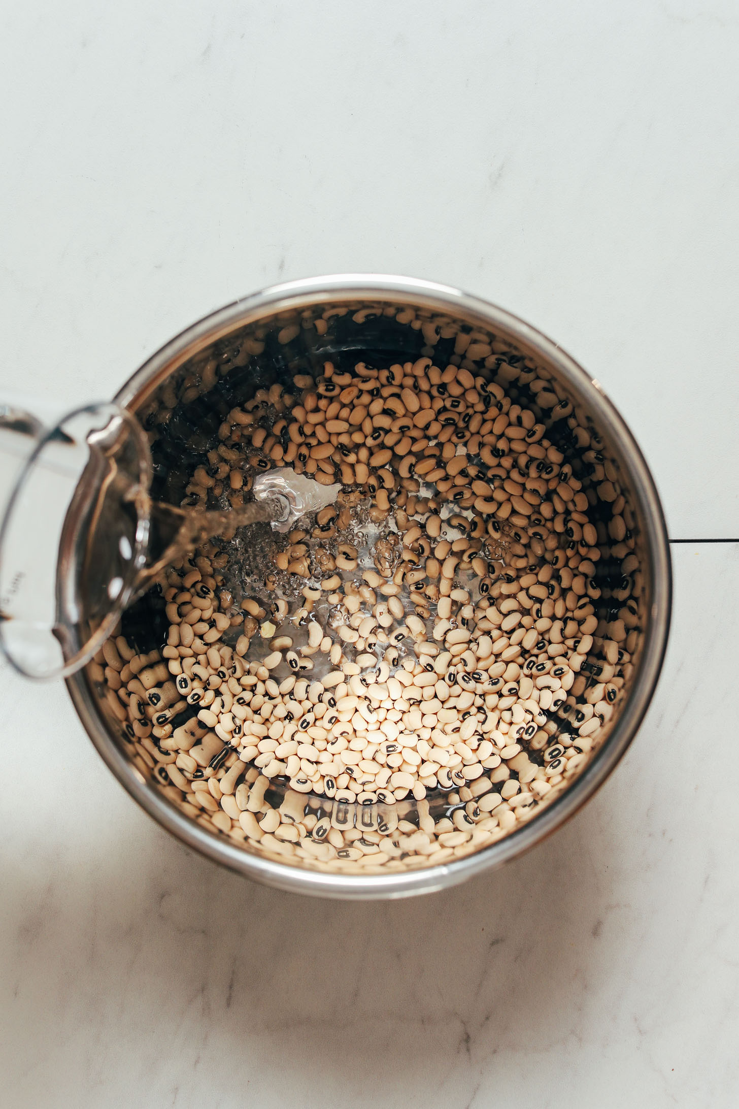 Pouring water into an Instant Pot of black eyed peas