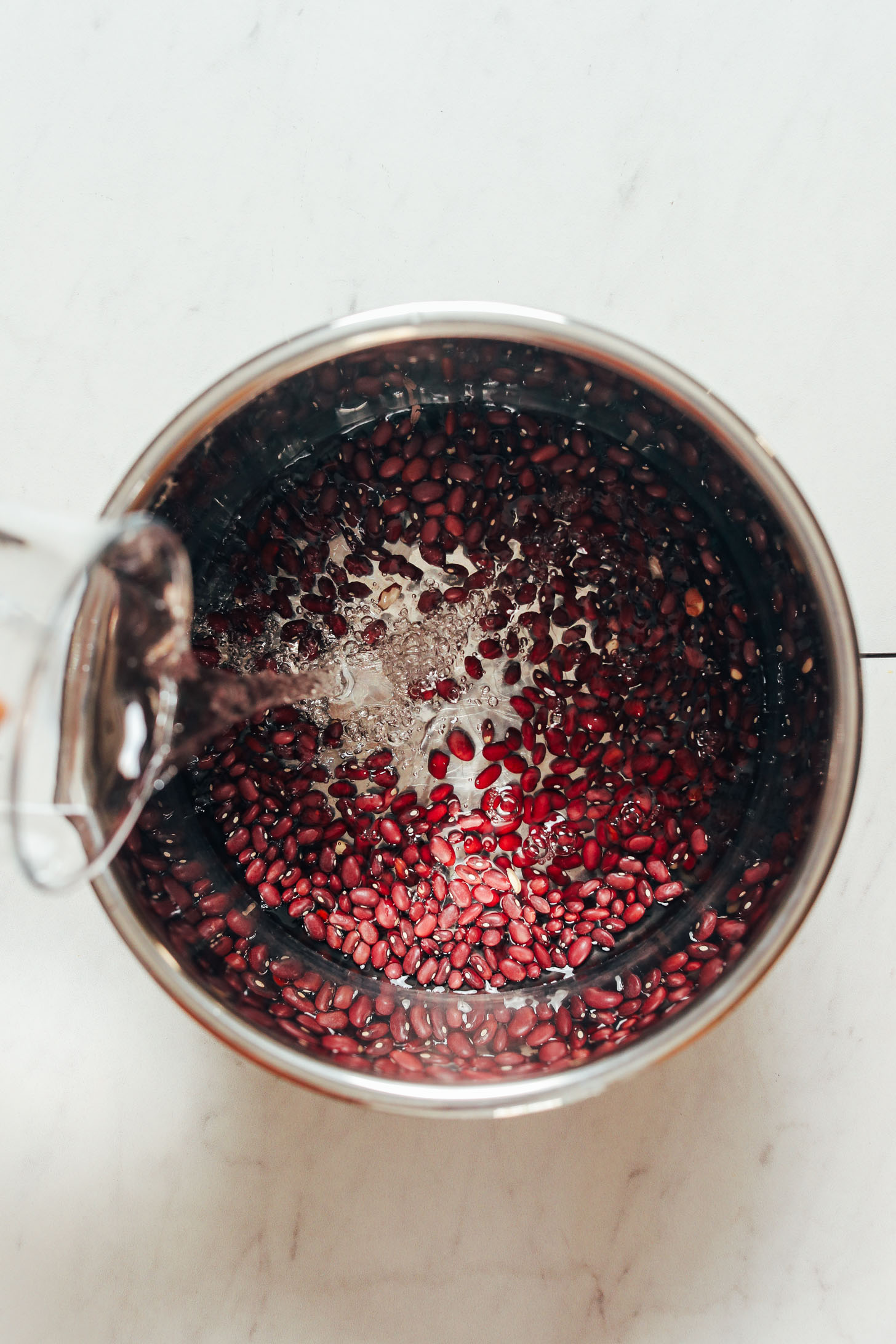 Pouring water into an Instant Pot of dry red beans