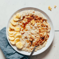 Bowl of rolled oats topped with banana, brown sugar, and walnuts